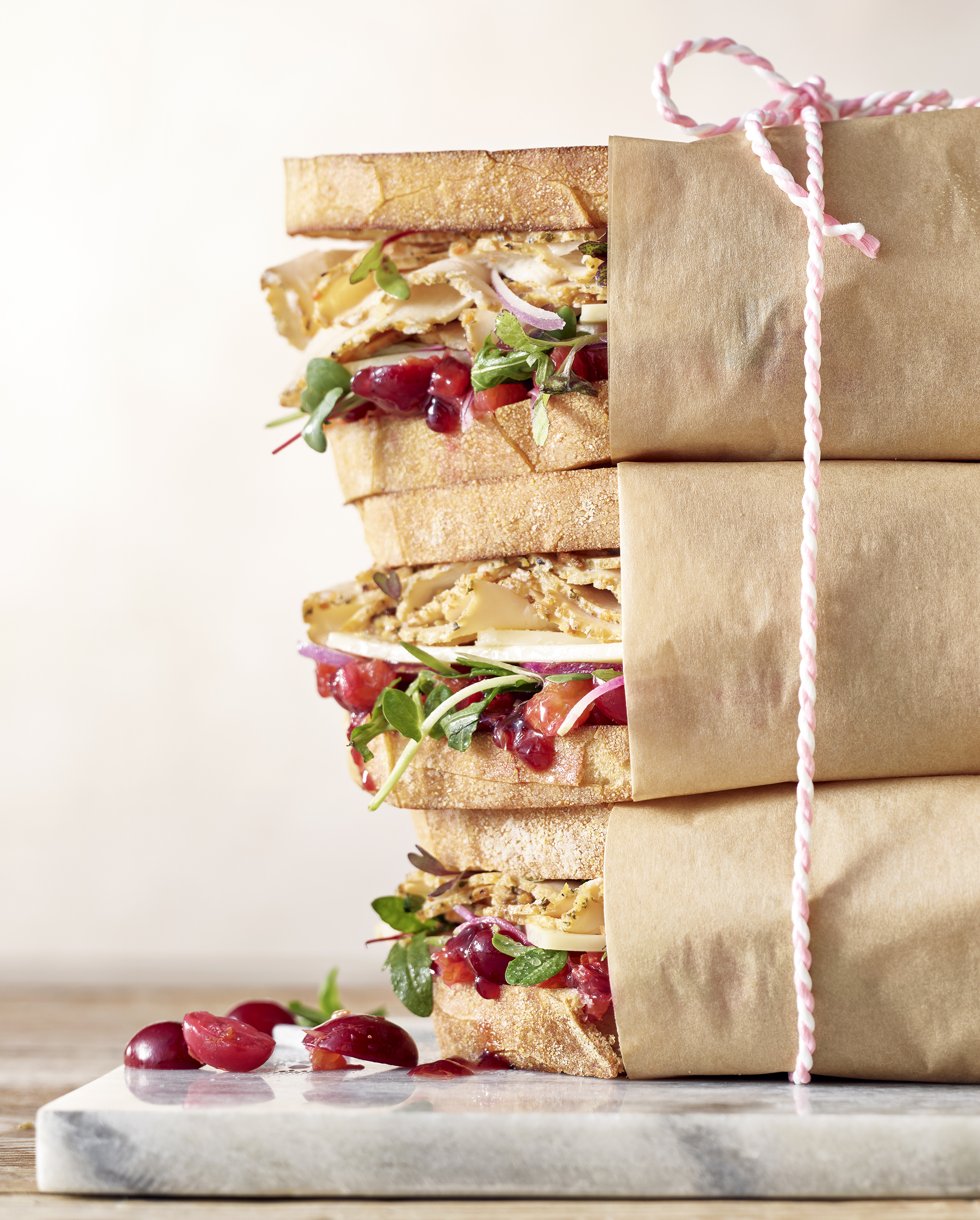 Stack of three turkey sandwiches on white bread wrapped in brown butcher paper with a pink string tying them together.