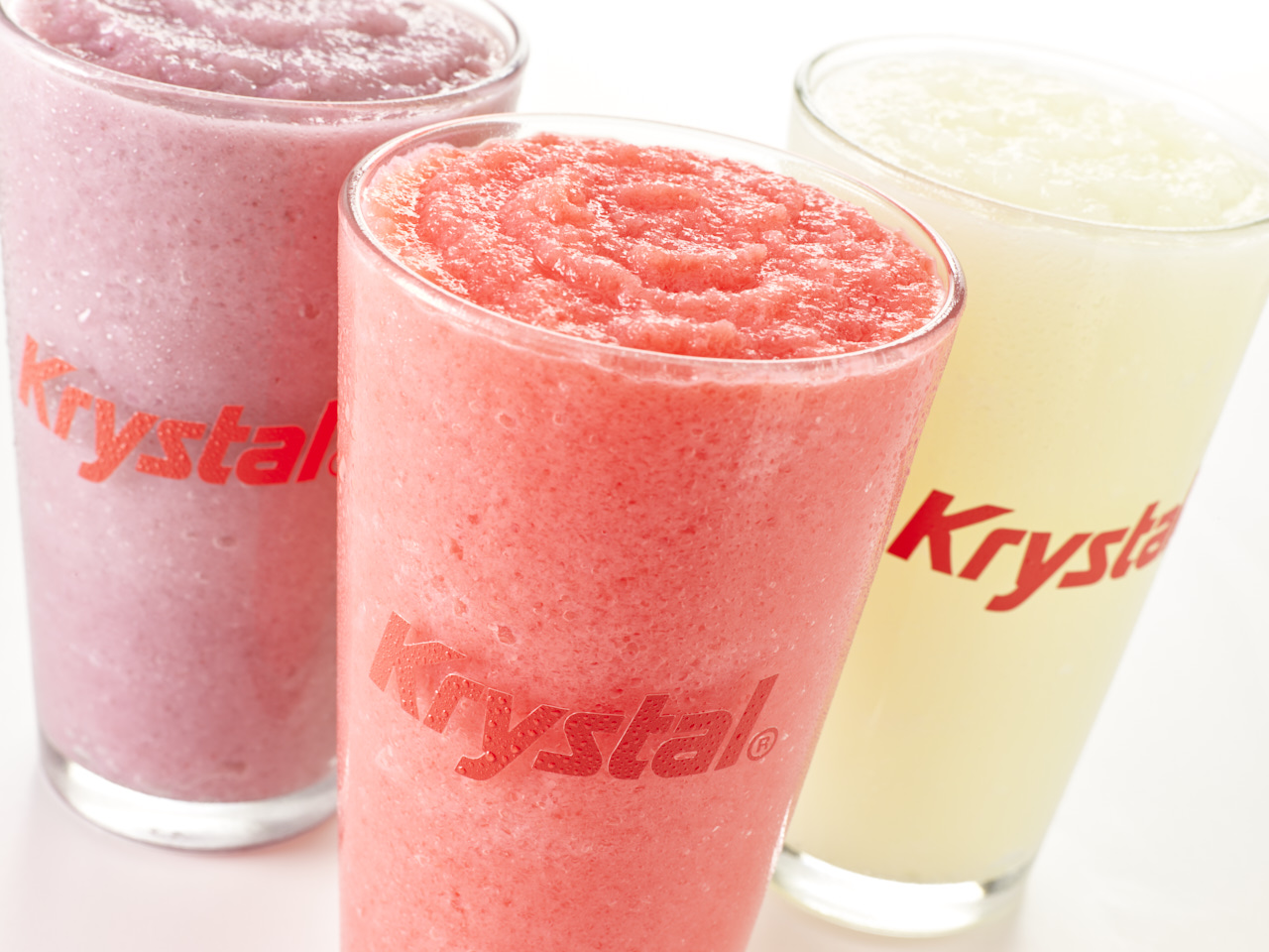 Raspberry, Strawberry, and Citrus slushies in clear glass Krystal cups.